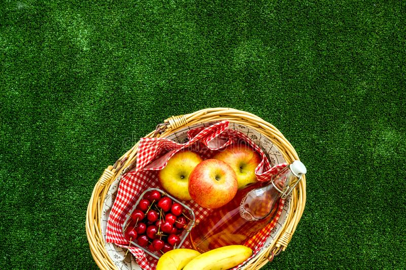 Picnic in summer with products, apples, banana, cherry, drinks on green grass texture background top view space for text. Basket with food. Picnic in summer with stock photography