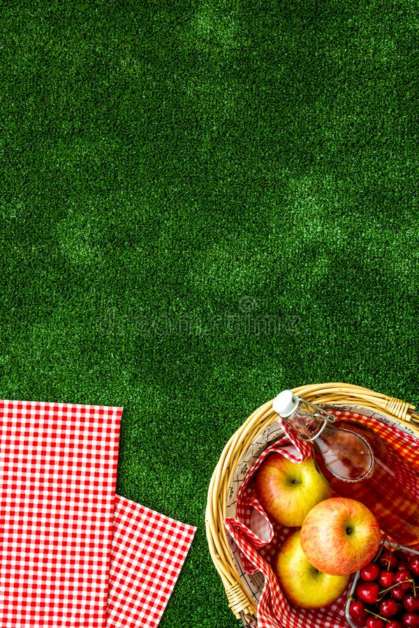 Picnic in summer with products, apples, cherry, drinks on green grass texture background top view space for text. Basket with food. Picnic in summer with stock photo
