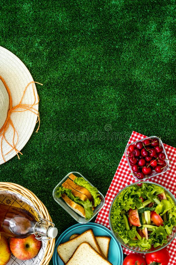 Picnic in summer with products, sandwich, salad, fruits, drink and hat on green grass texture background top view mockup. Basket with food. Picnic in summer with royalty free stock photos