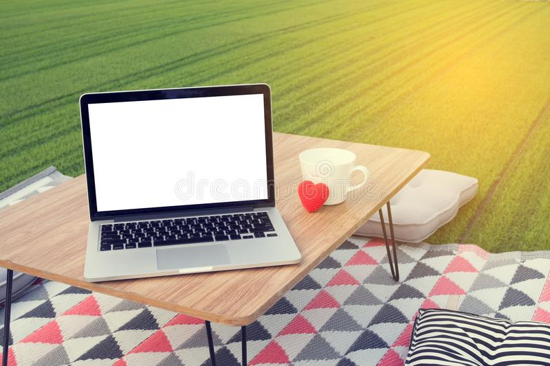 Picnic table with blank screen on laptop and white coffee cup, r. Ed heart shape at green lawn garden. concept of workplace in holiday. view from front notebook royalty free stock photography