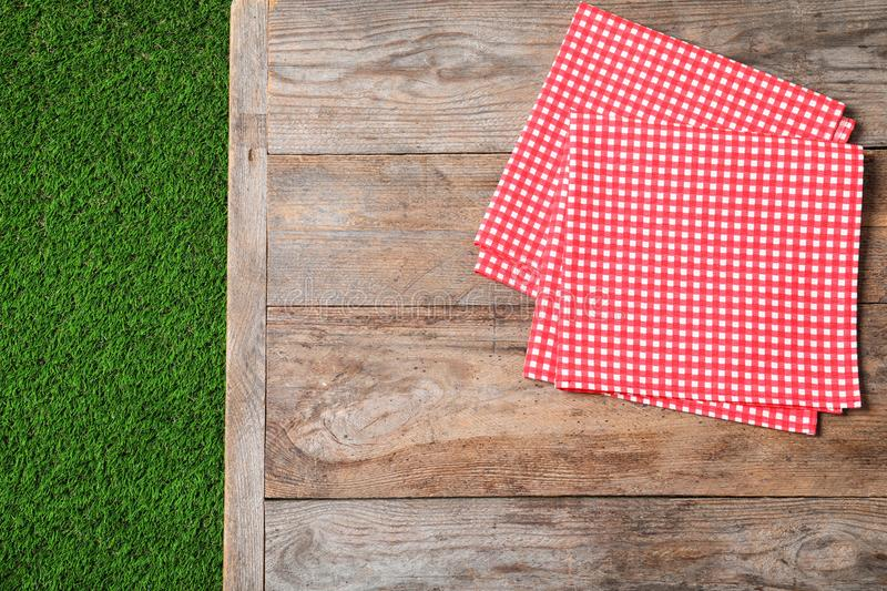 Picnic table with checkered napkins on grass. Space for text. Picnic table with checkered napkins on grass, top view. Space for text royalty free stock image