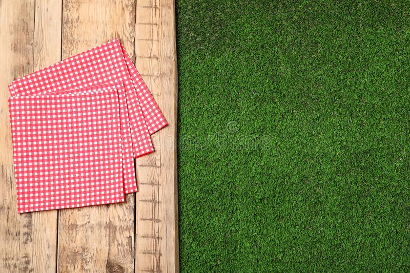 Picnic table with checkered napkins on grass. Space for text. Picnic table with checkered napkins on grass, top view. Space for text stock photos