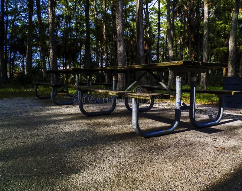 Picnic Table on a Concrete Pad in a Public Park. Public Park concrete pad with two wooden picnic tables. Wooden picnic tables with metal frames in shaded area at royalty free stock image