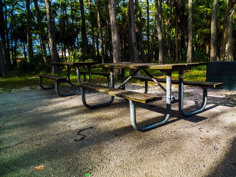 Picnic Table on a Concrete Pad in a Public Park. Public Park concrete pad with two wooden picnic tables. Wooden picnic tables with metal frames in shaded area at royalty free stock images