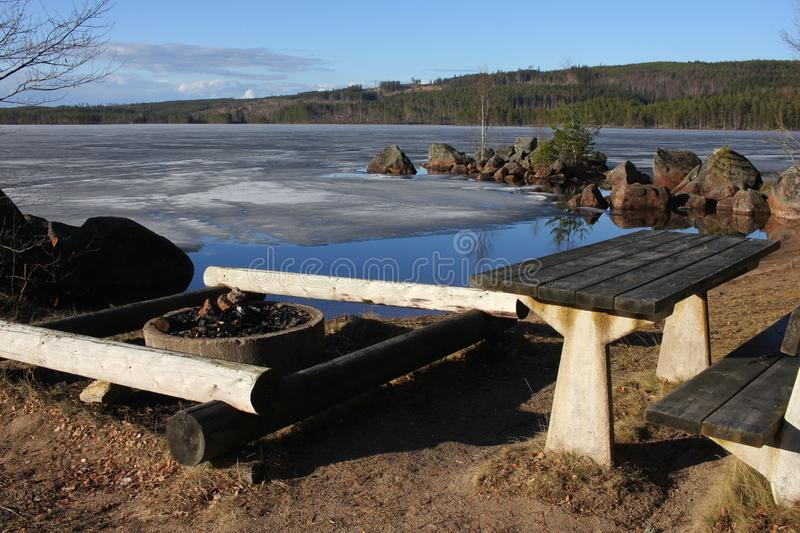 Picnic table and fireplace by a lake stock image
