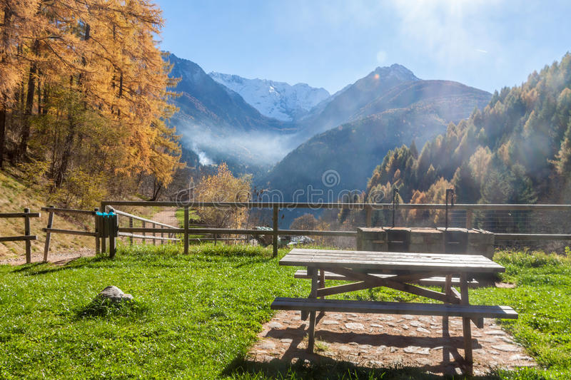 Picnic table in front of a autumnal panorama. In front of mountains stock image
