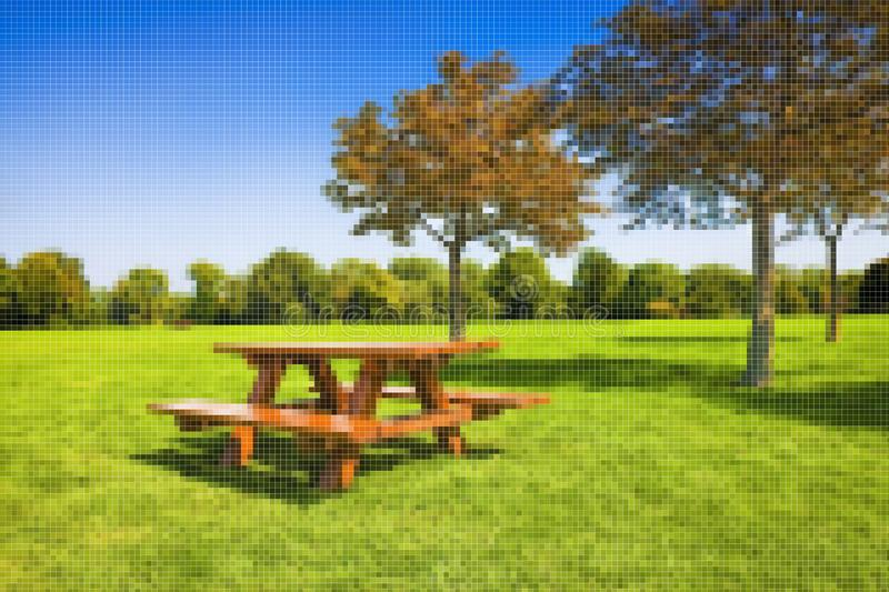Picnic table on a green meadow with trees on background - Concept image with pixelation effect.  royalty free stock photos