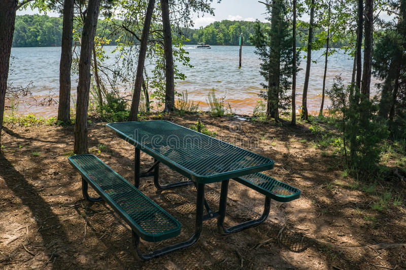 Picnic Table by Smith Mountain Lake. Franklin County, VA – May 29tht: Picnic table in woodland setting by Smith Mountain located in Smith Mountain Lake stock image