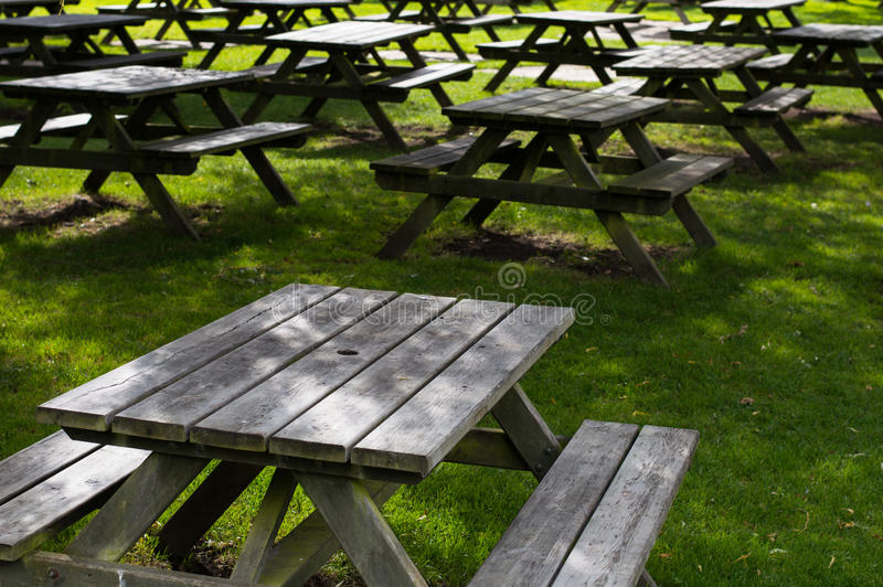 Picnic tables on the grass royalty free stock photography