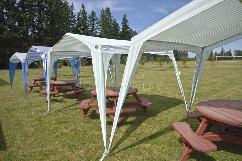 Picnic tables and tent gazebos on outdoor lawn. royalty free stock photography