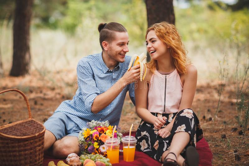 Picnic time. Love and tenderness, dating, romance, lifestyle concept. Picnic - Young couple in spring meadow. royalty free stock photo