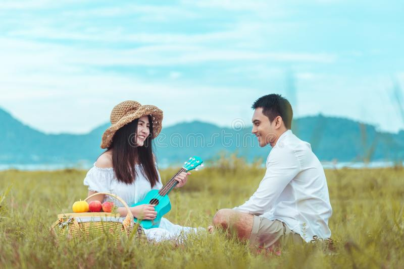 Picnic time. Young couple having fun with guitar on picnic in the park. Love and tenderness, dating, romance, lifestyle concept royalty free stock photos