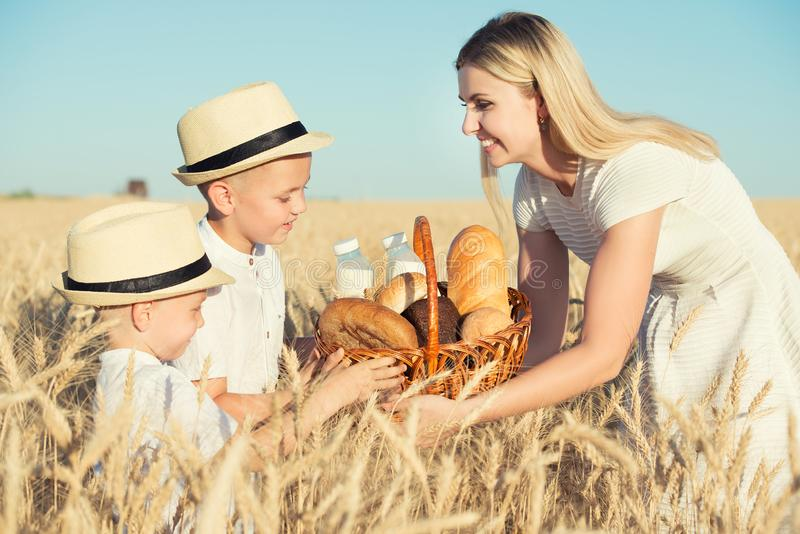 Mother gives children a basket with fresh bread and milk. A picnic on a wheat field. stock photography
