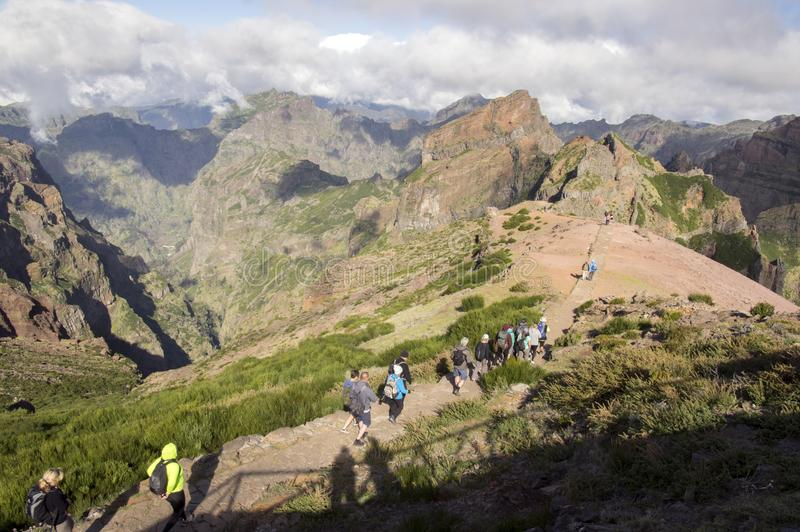 Pico Ariero / MADEIRA island, PORTUGAL - April 21, 2017: Groups of tourists hiking on touristic trail from peak Pico Ariero to P. Ico Ruivo stock photo