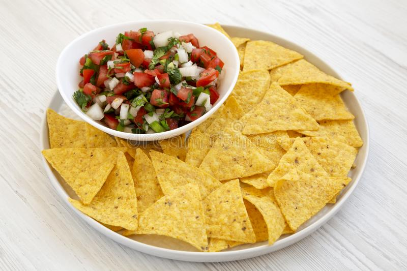 Pico de Gallo with gluten free tortilla chips on a white wooden background, side view stock photo