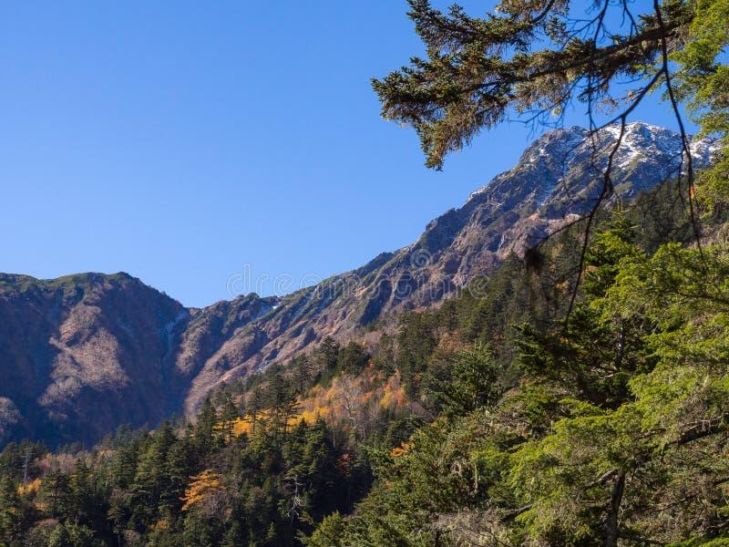 Pico de montaña de la nieve en la distancia con el cielo azul claro imagenes de archivo