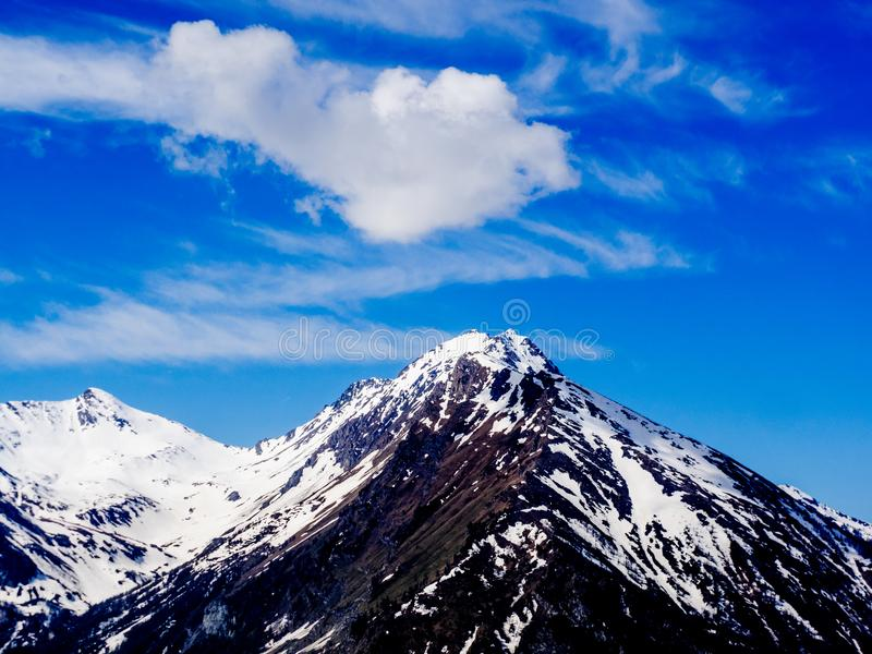 Pico de montaña en las montañas con las nubes en el top imágenes de archivo libres de regalías