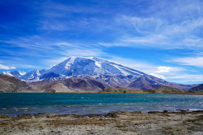 Pico de Muztagata e lago Karakul no outono foto de stock