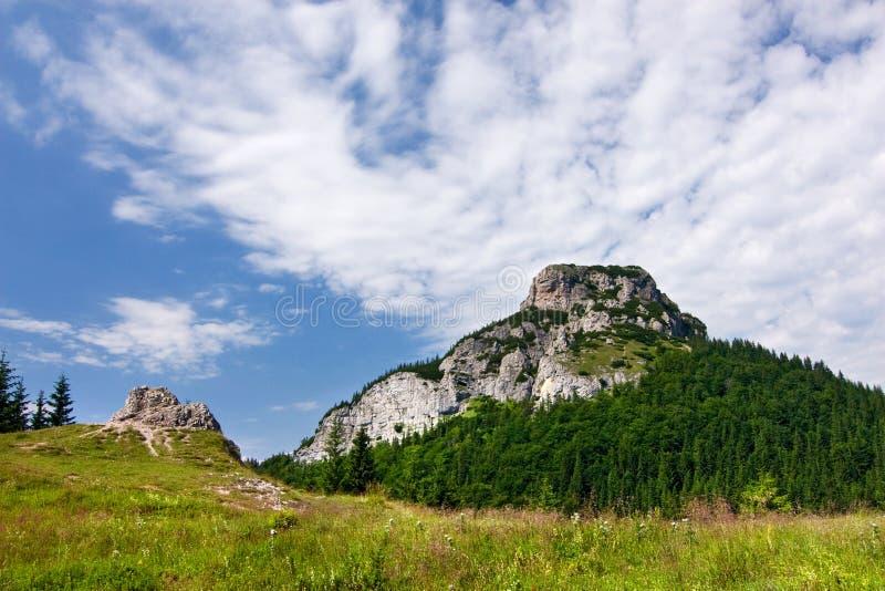 Pico pedregoso y cielo azul con las nubes imagen de archivo