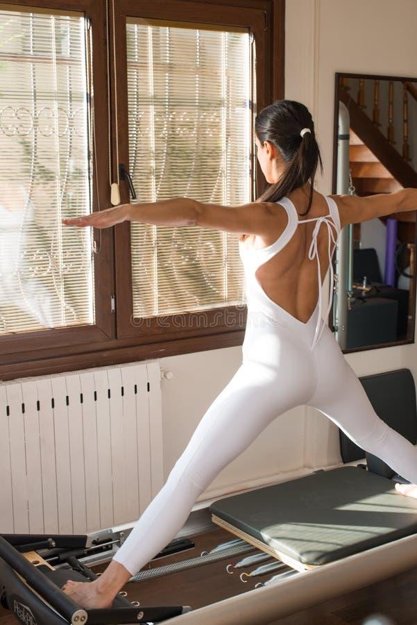 Pico Pilates - instructor Exercising de Pilates en el reformador máximo de Pilates fotos de archivo