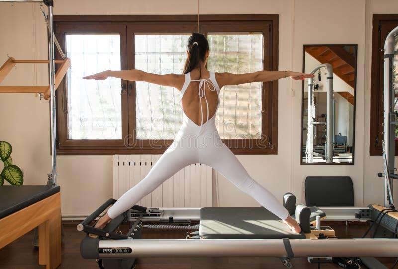 Pico Pilates - instructor Exercising de Pilates en el reformador máximo de Pilates imagenes de archivo
