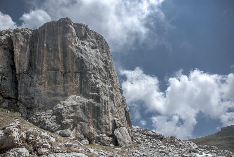 Pico rocoso de la montaña gigante entre las nubes imagen de archivo