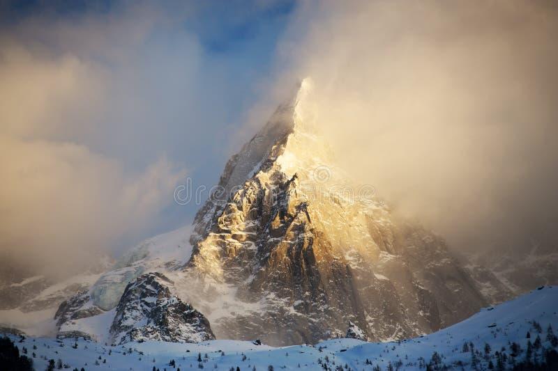 Pico rocoso en las montañas francesas en una puesta del sol en un día de invierno de niebla imagen de archivo