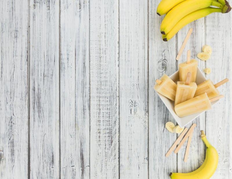Picolés da banana no fundo de madeira imagem de stock