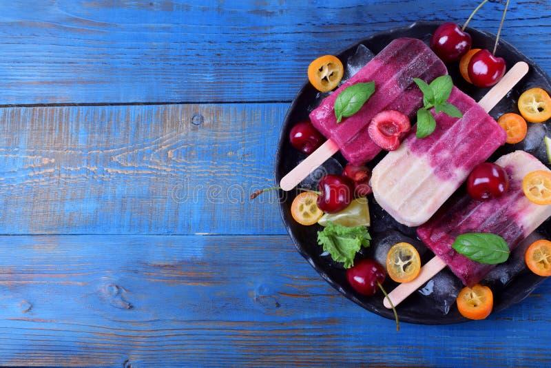 Picolés do fruto e da baga na placa com gelo, partes de kumquat, cal e cerejas e hortelã foto de stock royalty free