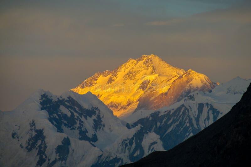 Picos da neve da cordilheira sob nuvens alaranjadas do por do sol imagem de stock royalty free