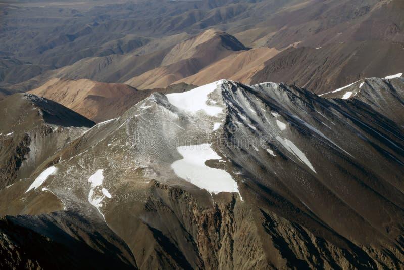 Picos das montanhas cobertas com o gelo e a neve imagem de stock