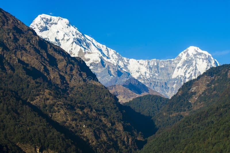 Picos de montaña con nieve en fondo del cielo azul imagen de archivo