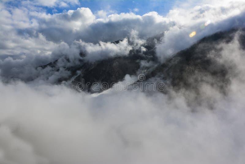 Picos de montaña cubiertos por las nubes fotografía de archivo libre de regalías