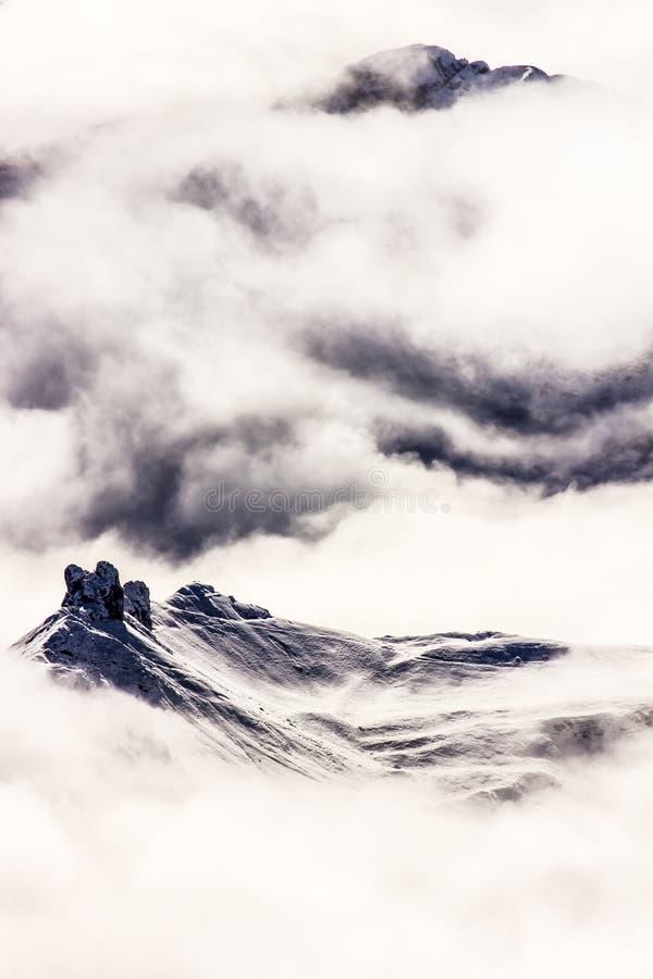Picos de montaña del invierno en las nubes de niebla, Minimalistic, Dolomit fotos de archivo libres de regalías