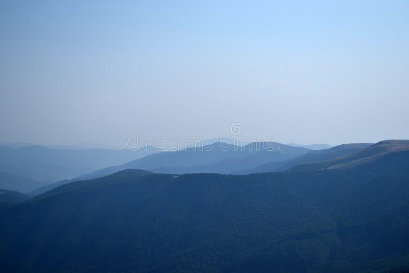 Picos de montaña en el cielo de la tarde del otoño, nubes foto de archivo