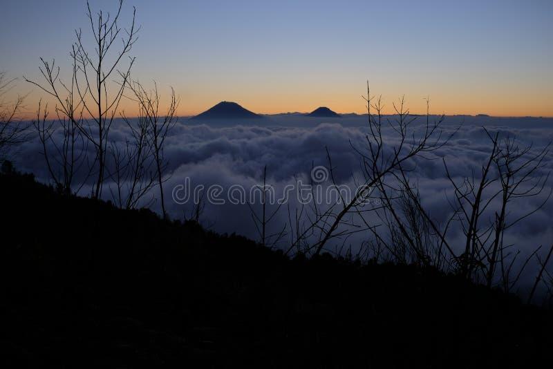 Picos de montaña de Sindoro y de Sumbing después de la puesta del sol foto de archivo