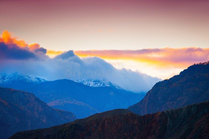 Picos de montanha com as nuvens no por do sol Altai, Sibéria, Rússia imagens de stock royalty free