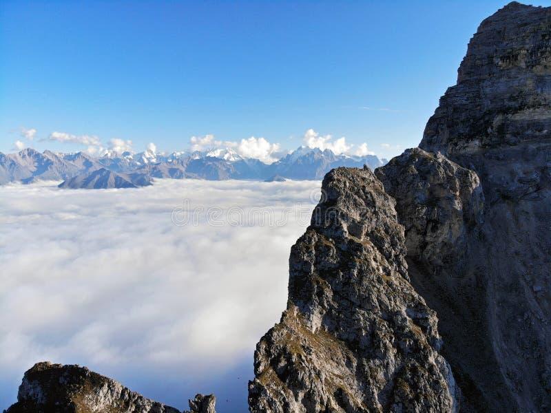 Picos de montanha do Cáucaso que eleva-se acima das nuvens Névoa no desfiladeiro da montanha imagens de stock