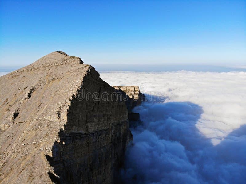 Picos de montanha do Cáucaso que eleva-se acima das nuvens Névoa no desfiladeiro da montanha fotografia de stock