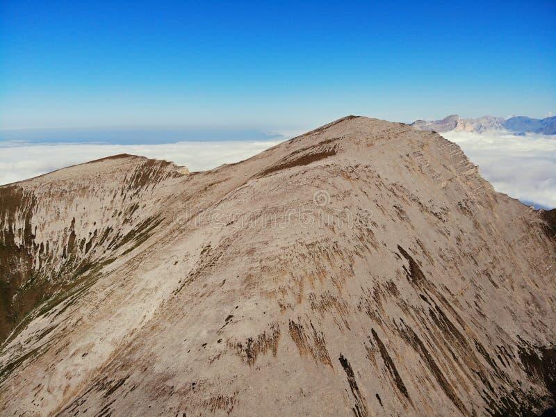 Picos de montanha do Cáucaso que eleva-se acima das nuvens Névoa no desfiladeiro da montanha foto de stock