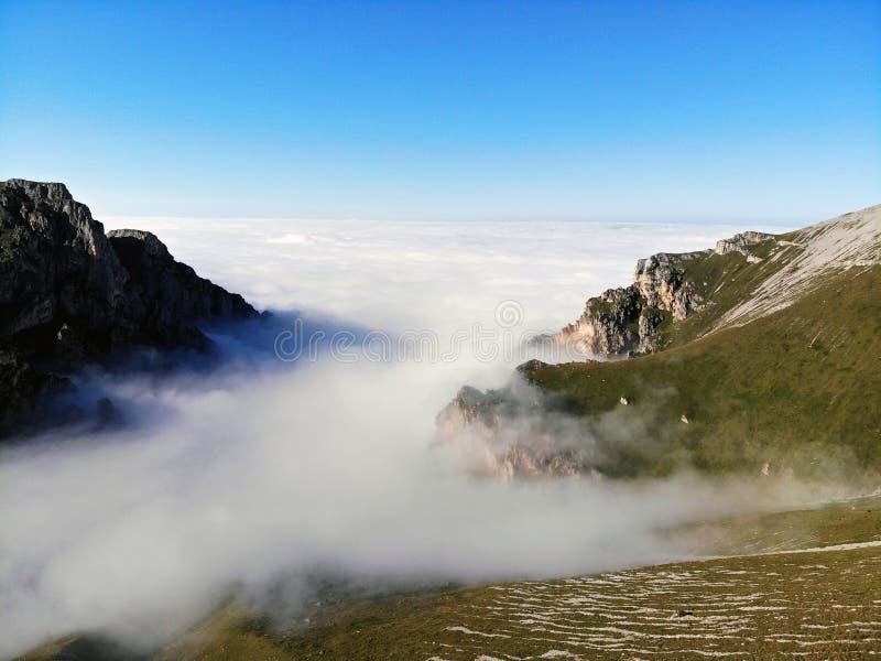 Picos de montanha do Cáucaso que eleva-se acima das nuvens Névoa no desfiladeiro da montanha imagem de stock