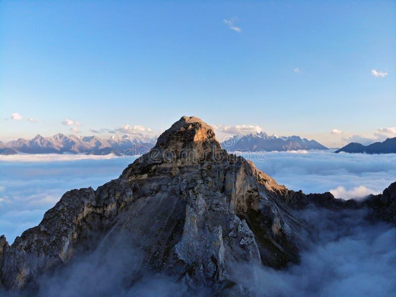 Picos de montanha do Cáucaso que eleva-se acima das nuvens Névoa no desfiladeiro da montanha foto de stock royalty free