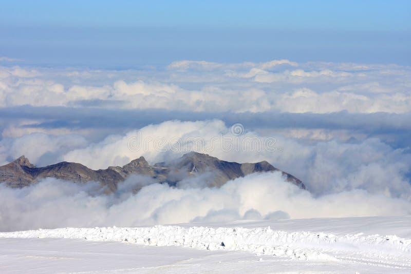 Picos de montanha sobre as nuvens no Jungfraujoch imagens de stock