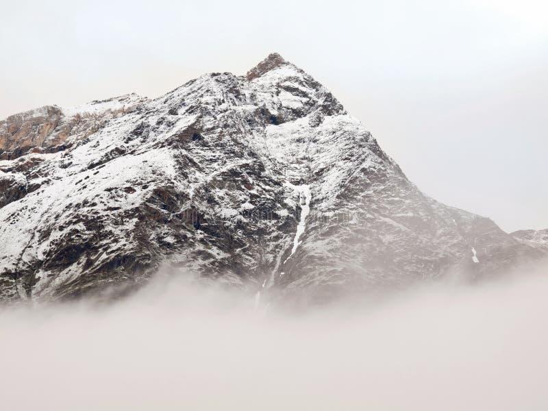 Picos nevado afiados de montanhas dos cumes acima do vale completamente da névoa cinzenta pesada fotos de stock