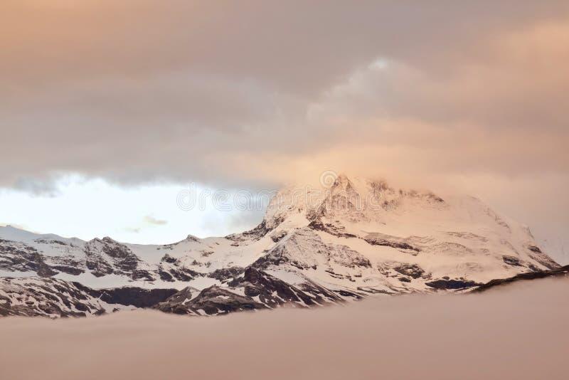 Picos nevado afiados de montanhas dos cumes acima do vale completamente da névoa cor-de-rosa e alaranjada pesada foto de stock