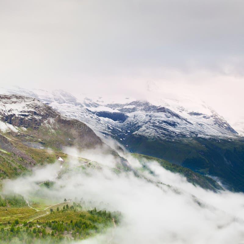 Picos nevado afiados de montanhas dos cumes acima do vale completamente da névoa pesada, fim do verão imagem de stock