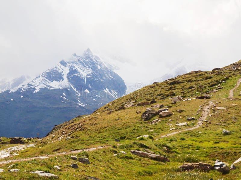 Picos nevado afiados de montanhas dos cumes acima do vale completamente da névoa pesada, fim do verão fotos de stock royalty free