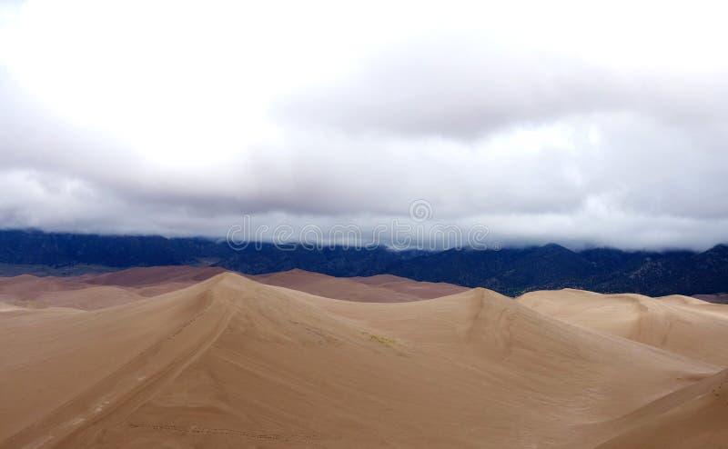 Picos nublados del alto contraste de las dunas de arena foto de archivo