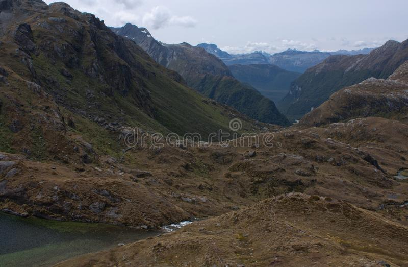Picos que miran a escondidas en la distancia detrás del valle en el gran paseo de Routeburn en Fiordland en Nueva Zelanda imagen de archivo