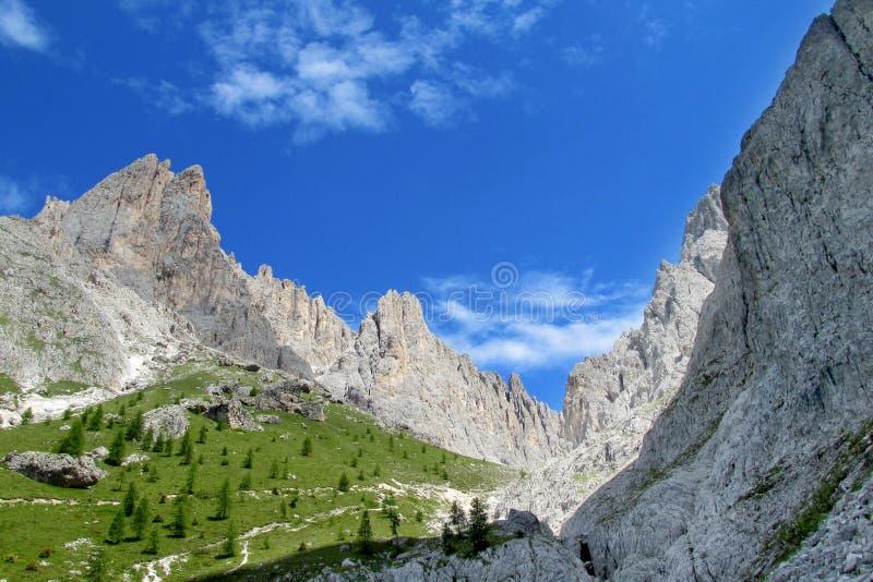 Picos rocosos hermosos de las dolomías sobre el valle verde foto de archivo